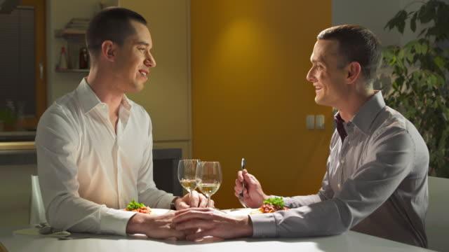 vídeos de stock, filmes e b-roll de hd: gay casal tendo jantar romântico - homossexualidade