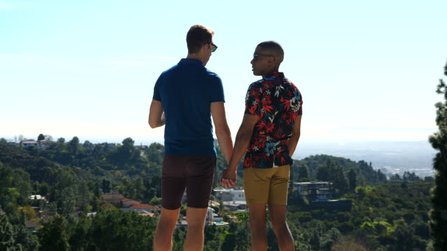 ms pan gay couple holding hands and looking at view while standing on deck of vacation rental - house rental stock videos & royalty-free footage