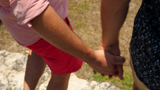 cu gay couple holding hands while walking on grounds of ancient mayapan ruins - geschichtlich stock-videos und b-roll-filmmaterial