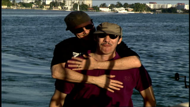 gay couple hugging and kissing on back of boat in miami florida - herumfahren stock-videos und b-roll-filmmaterial