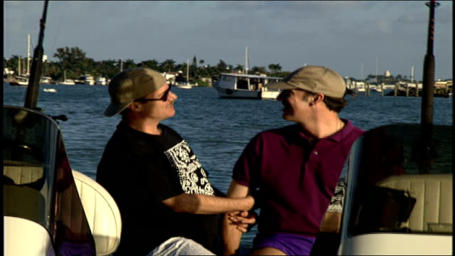 gay couple hugging kissing and talking on back of boat in miami florida - herumfahren stock-videos und b-roll-filmmaterial