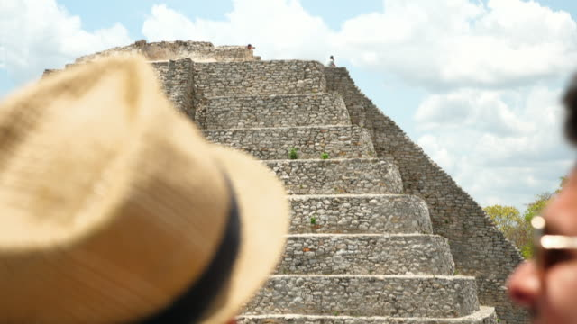 cu r/f gay couple in discussion while looking at pyramid during visit to mayapan ruins - harmony stock videos & royalty-free footage