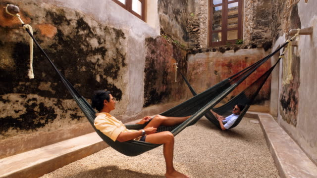 TD Gay couple in discussion while relaxing in hammocks at luxury resort