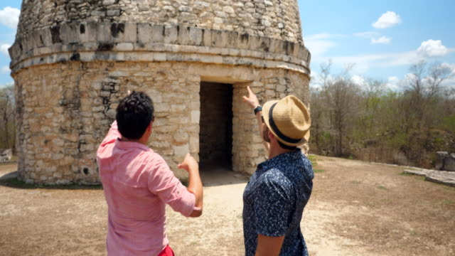 vídeos de stock e filmes b-roll de ms gay couple in discussion while visiting mayapan ruins during vacation - maia