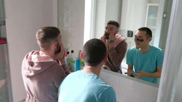 vídeos de stock, filmes e b-roll de casal gay em frente ao espelho do banheiro fazendo tratamento facial - boyfriend