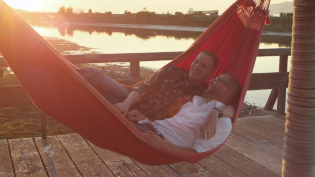 vídeos de stock, filmes e b-roll de ms gay couple in hammock on dock at sunset embracing and laughing - rede de dormir