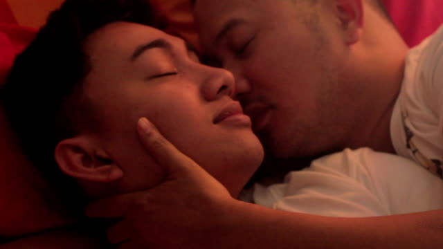 gay couple kiss in bed - kissing stock videos & royalty-free footage