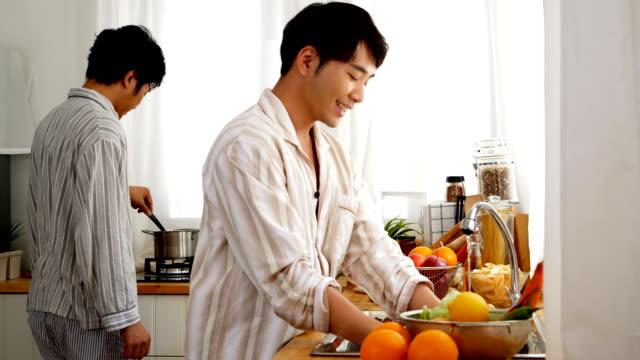 同性カップルが家で一緒に朝食を作るします。ゲイ、同性愛者、ライフ スタイルとの関係の概念を持つ人々。 - 2人点の映像素材/bロール