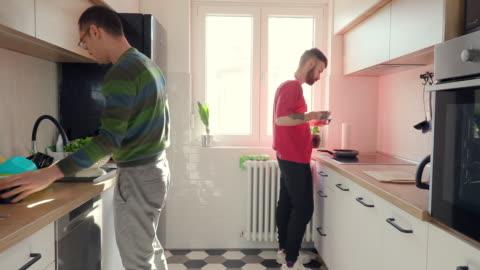 vídeos y material grabado en eventos de stock de pareja gay haciendo el desayuno juntos en la cocina - en búsqueda