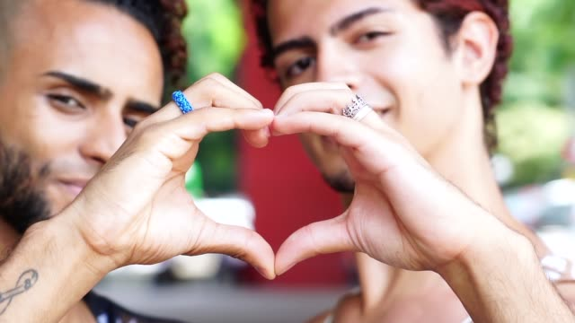 Gay couple making heart shape with hands