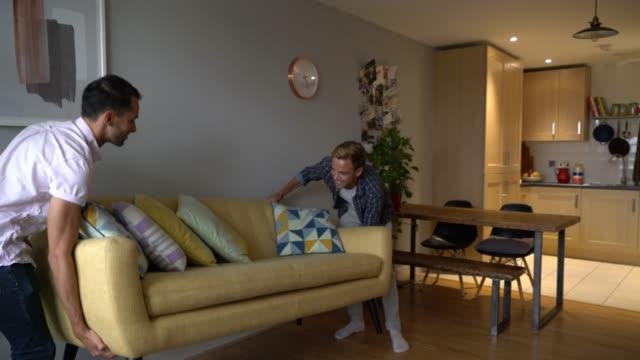 vídeos de stock, filmes e b-roll de pares alegres que movem-se dentro a seu sofá carreg home novo e assento nele que abraça e que sorri - homossexualidade