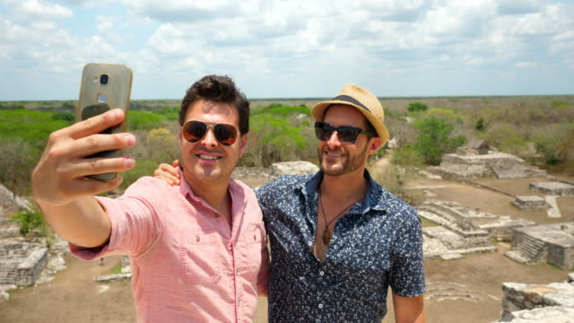 vídeos de stock, filmes e b-roll de ms gay couple posing for selfie while exploring the mayapan ruins - parte de uma série