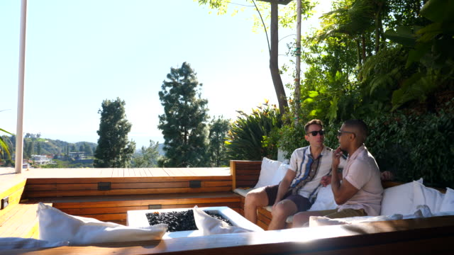 ws gay couple relaxing on outdoor furniture in backyard - house rental stock videos & royalty-free footage