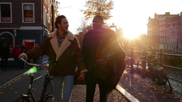 gay par ridning cyklar i höst eftermiddag i staden - rasblandat homosexuella par njuta av helgen tillsammans - amsterdam bildbanksvideor och videomaterial från bakom kulisserna