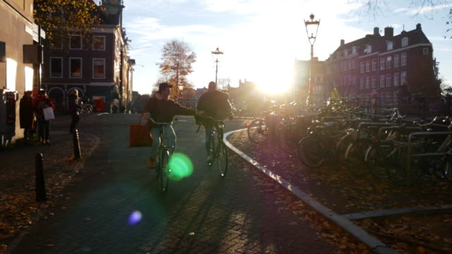 gay couple riding bicycles in autumn afternoon in the city - interracial homosexual couple enjoying weekend together - amsterdam stock videos & royalty-free footage