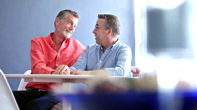 gay couple sitting, talking - cinquantenne video stock e b–roll