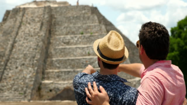 ms gay couple standing in awe of mayapan ruins during vacation - travel destinations stock videos & royalty-free footage