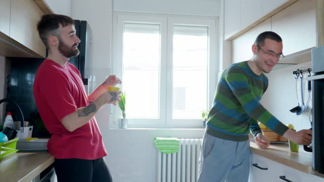 gay couple standing in the kitchen and having coffee - mug stock videos & royalty-free footage