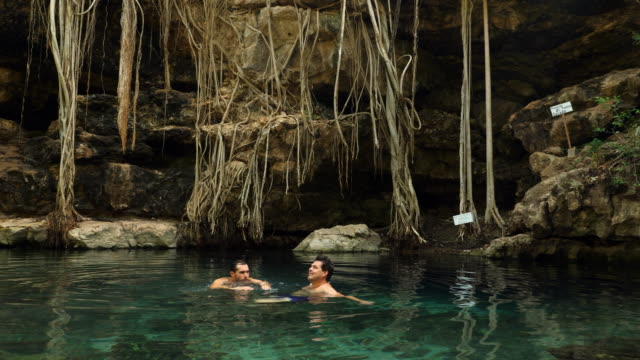 MS TD Gay couple swimming in cenote together while on vacation