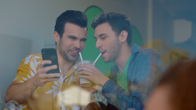 cu. a gay couple take a selfie of sharing a milkshake with two straws - only men stock videos & royalty-free footage