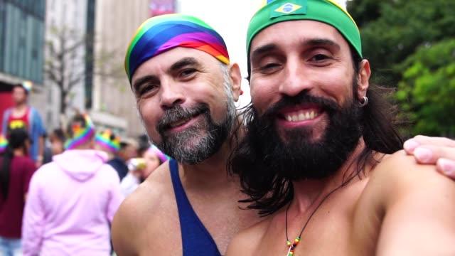 vídeos de stock e filmes b-roll de gay couple taking a selfie at gay parade - 50 54 anos