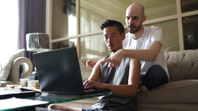 gay couple using laptop at home - completely bald stock videos & royalty-free footage