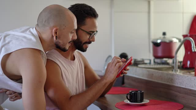 gay couple using smartphone and enjoying a coffee - breakfast stock videos & royalty-free footage