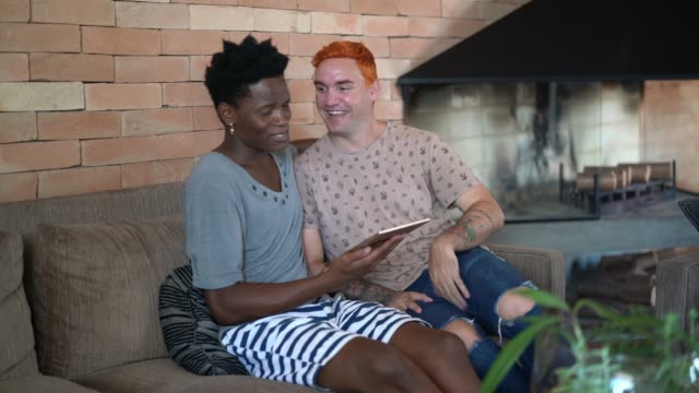 gay couple using tablet at home - married stock videos & royalty-free footage