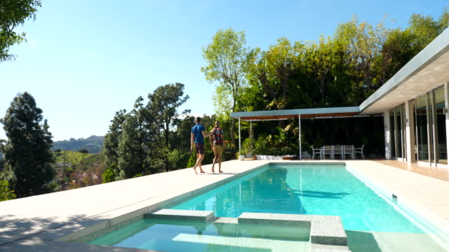 ws gay couple walking into modern house from pool deck on sunny afternoon - home ownership stock videos & royalty-free footage