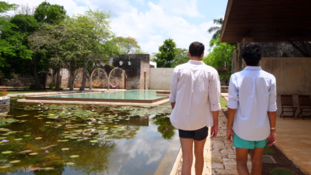 MS Gay couple walking to pool from hotel room while on vacation at luxury resort