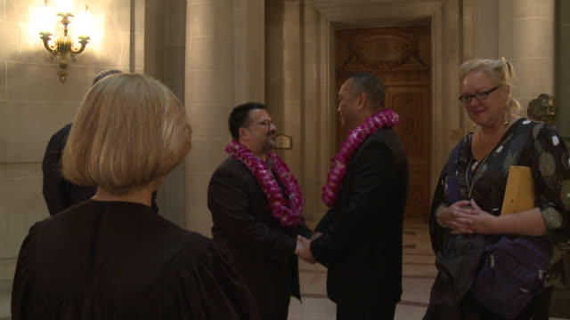 gay couple wearing leis with friends/ pan ms men facing each other holding hands and reciting wedding vows at san francisco city hall/ san francisco... - ziegenbart stock-videos und b-roll-filmmaterial