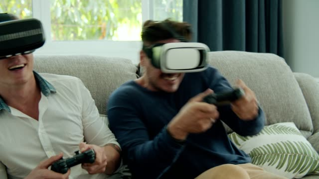 gay couple wearing vr glasses and playing game - handheld video game stock videos & royalty-free footage