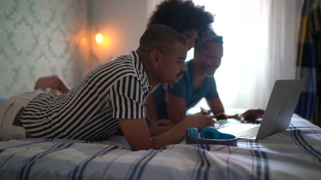 ベッドでラップトップで映画を見てゲイの家族 - リアルライフ 点の映像素材/bロール