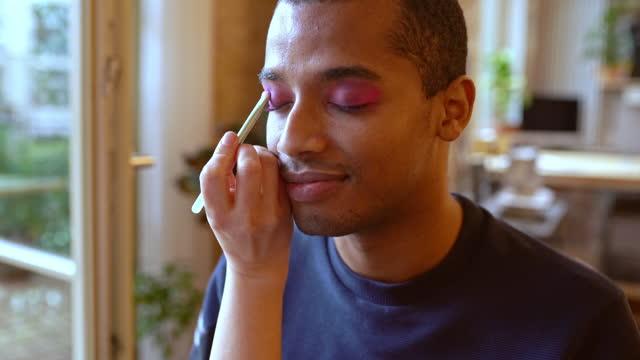 stockvideo's en b-roll-footage met gay friend applying lipstick to female roommate in living room - etniciteit