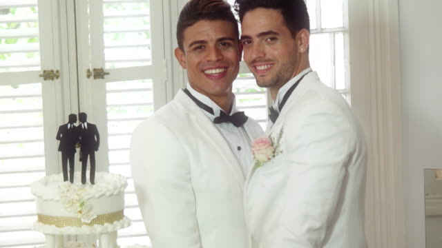 Gay grooms couple pose with wedding cake.