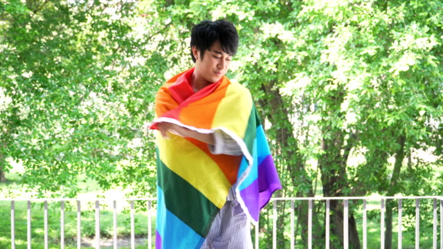 Gay handsome Boy Holding Rainbow Flag by feeling happiness
