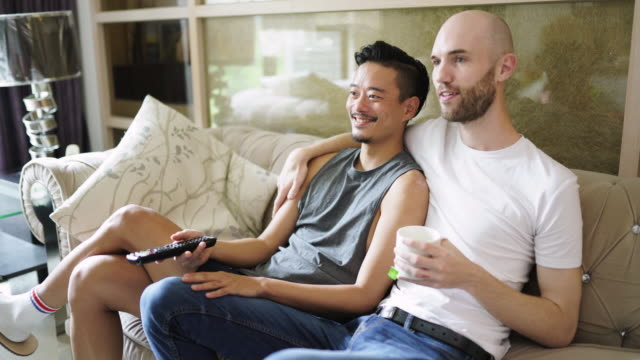 gay lovers watching tv in the living room - comfortable stock videos & royalty-free footage