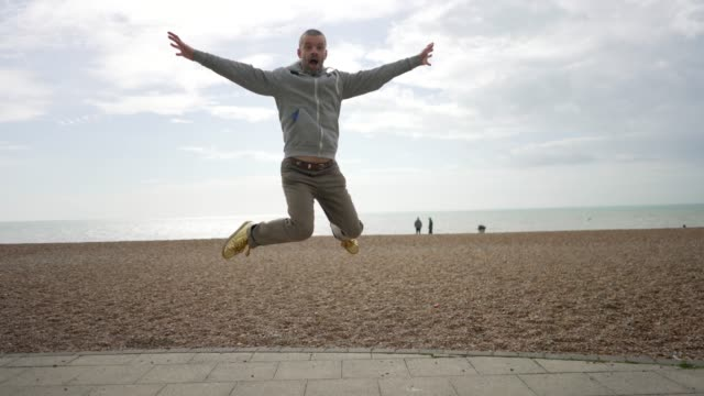 a gay man doing a jump shot on the beach. - jump shot stock videos and b-roll footage