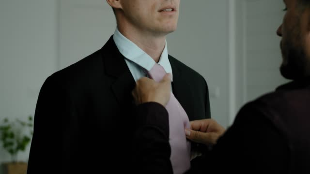 gay man helping to put on a neck tie to his boyfriend - body care stock videos & royalty-free footage