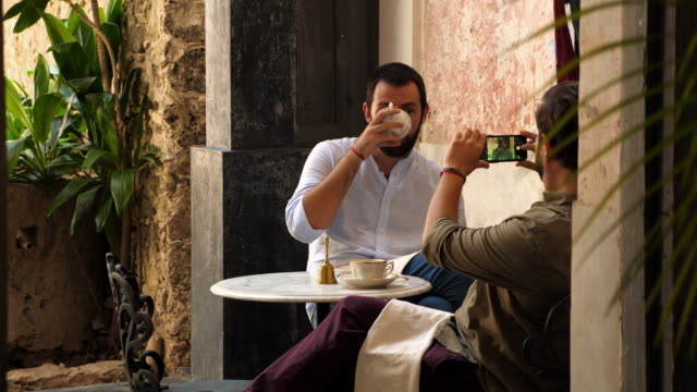 MS Gay man taking picture of partner with smartphone while sitting in outdoor cafe during vacation