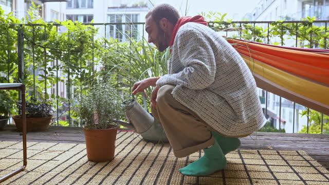 gay man watering potted plant at patio - 水撒き点の映像素材/bロール