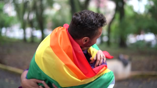 gay married couple enjoying a day at park - rainbow flag stock videos & royalty-free footage
