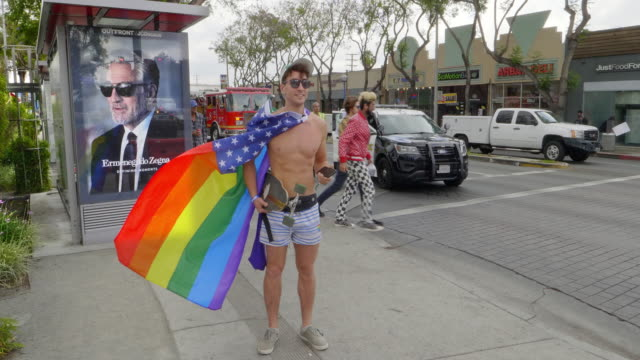 A gay member of LGBT community with rainbow flag during the pride parade in West Hollywood, Los Angeles, California, 4K