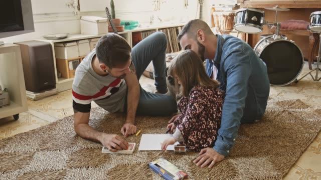 vídeos de stock e filmes b-roll de gay parents assisting daughter with drawing at home - pais