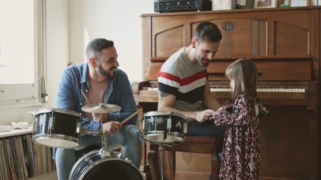 vídeos y material grabado en eventos de stock de padres gays compartiendo música con su hija en casa - juguete
