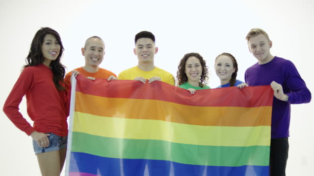 vídeos de stock, filmes e b-roll de gay pride grupo em pé na unidade segurando bandeira do orgulho gay - evento anual