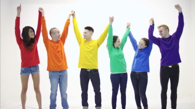 gay pride group standing in unity holding hands in victory - human rights stock videos and b-roll footage