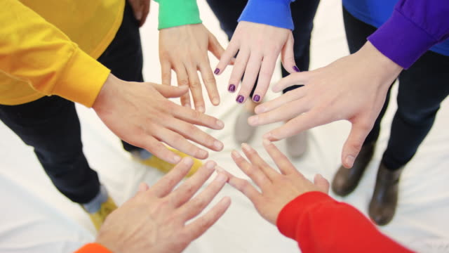 Gay Pride Gruppe stand im Einklang mit der Nahaufnahme der Hände