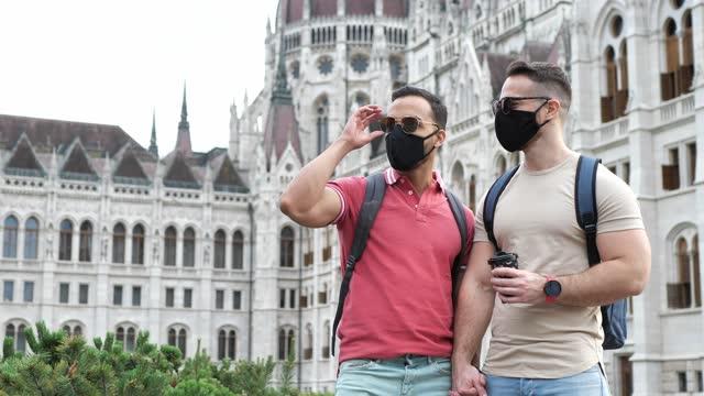 vídeos y material grabado en eventos de stock de turistas gays con máscaras faciales, fotografiándose unos a otros cerca de un edificio famoso - budapest