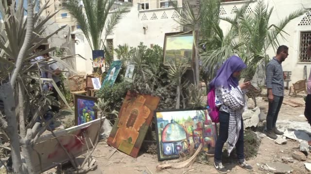 gaza artists display their work amid the rubble of the village of arts and crafts which was damaged by israeli airstrikes on gaza city on saturday - gaza city stock videos & royalty-free footage